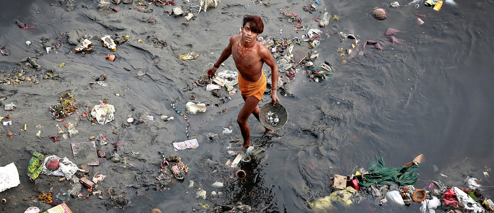 A man sifts through rubbish in the Yamuna river in Delhi, India, October 31, 2017. REUTERS/Cathal McNaughton     TPX IMAGES OF THE DAY - RC17BC46ED60