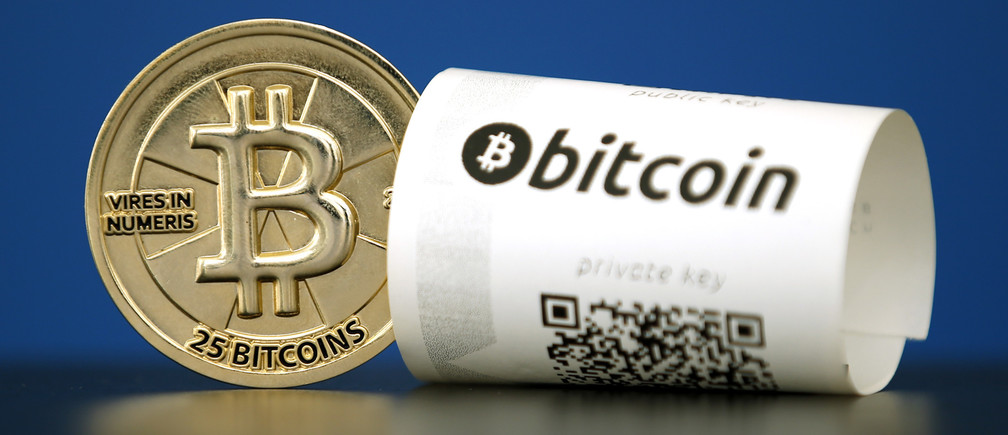"A Bitcoin (virtual currency) paper wallet with QR codes and a coin are seen in an illustration picture taken at La Maison du Bitcoin in Paris, France, May 27, 2015. British authorities have come out in support of digital currencies in the name of promoting financial innovation, while proposing that regulations should be drawn up to prevent their use in crime. But it is technophiles who are leading the drive to make London a real-world hub for trade in web-based ""cryptocurrencies"", of which bitcoin is the original and still most popular.   Picture taken May 27, 2015.  REUTERS/Benoit Tessier - RTX1EWTP"