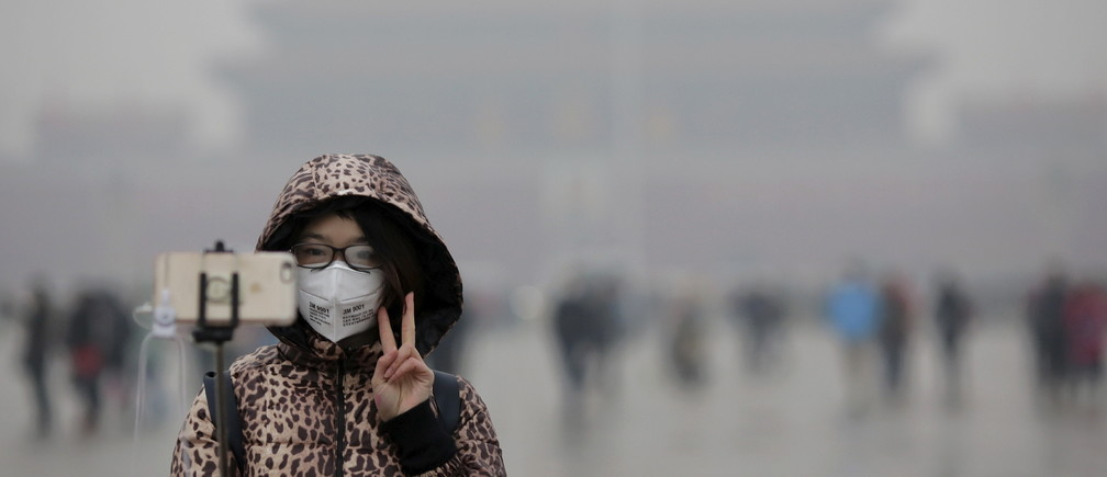 "A woman wearing a protective mask has her picture taken just after a flag-raising ceremony amid heavy smog at the Tiananmen Square, after the city issued its first ever ""red alert"" for air pollution, in Beijing December 9, 2015.   REUTERS/Damir Sagolj - GF10000259384"