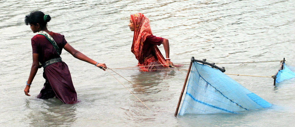 Two Bangladeshi women catch shrimp from a river with nets in Shyamnagar in Satkhira district about 350km (220 miles) southwest of the capital Dhaka June 17, 2005.