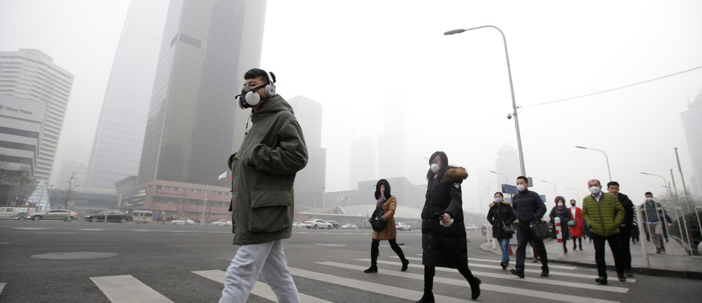 A man wearing a respiratory protection mask walks toward an office building during the smog after a red alert was issued for heavy air pollution in Beijing's central business district, China, December 21, 2016. REUTERS/Jason Lee     TPX IMAGES OF THE DAY - RTX2VY34