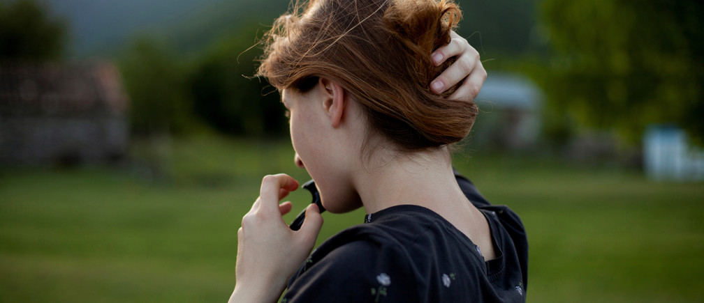"Mariam Kebadze, 16, fixes her hair during an evening walk along Alazani river in Jokolo village of Pankisi, Georgia, May 31, 2019. Mariam used to live with her father in Telavi and moved to Pankisi where she now lives and studies to support her mother Leila Achishvili who is running a guesthouse. ""It's really boring sometimes here, there's not much to do in the village because it's the same routine all the time - school, classes, jogging by the river sometimes. Girls don't go outside at night because they are embarrassed and sometimes I really miss going for a walk in the evening, I like nights,"" she said. ""One of my dreams is to live somewhere in the mountains, maybe in Switzerland. I read about a music festival in a forest there with beautiful lights at night, and people just dancing and laughing, they are so free and cheerful."" REUTERS/Ekaterina Anchevskaya     SEARCH ""PANKISI WOMEN"" FOR THIS STORY. SEARCH ""WIDER IMAGE"" FOR ALL STORIES. - RC1FFD6E02B0"