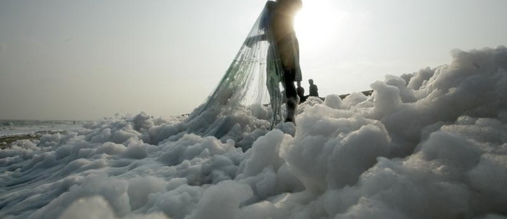 A fisherman pulls his net on the shore filled with foam at the Marina beach in Chennai, India, November 23, 2018. REUTERS/P. Ravikumar - RC13A7875F00