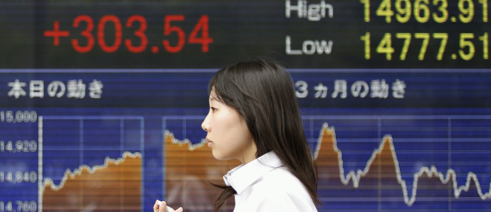 A woman holding her mobile phone walks past an electronic board showing Japan's Nikkei average outside a brokerage in Tokyo June 2, 2014.