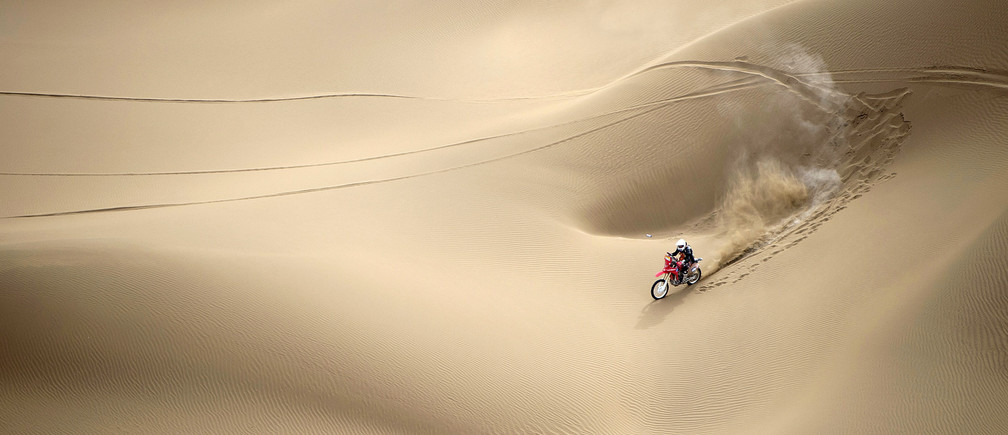 Wang Yirong of Hebei province rides his motorcycle in a desert during the China Taklimakan Rally and CCR Xinjiang Station, in Shanshan, Xinjiang Uighur Autonomous Region May 31, 2014. REUTERS/China Daily (CHINA - Tags: SPORT MOTORSPORT TPX IMAGES OF THE DAY) C