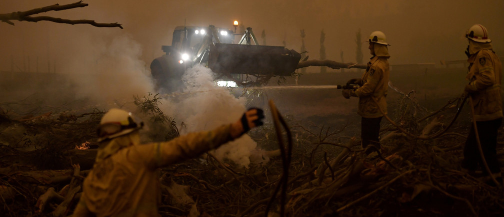 A burning gum tree is felled to stop it from falling on a car in Corbago, as bushfires continue in New South Wales, Australia January 5, 2020. REUTERS/Tracey Nearmy REFILE - CORRECTING YEAR - RC2M9E9PPV4M