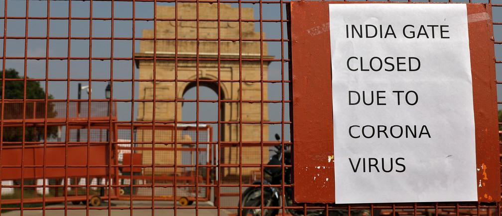 Un cartel pegado en una barricada de seguridad se ve después de que el monumento de guerra de la Puerta de la India se cerrara para los visitantes en medio de las medidas de prevención del coronavirus en Nueva Delhi (India), el 19 de marzo de 2020.