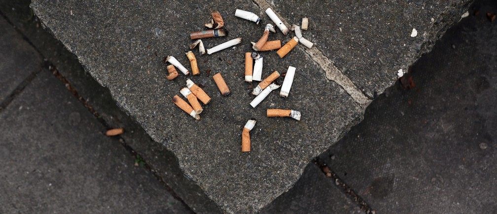 Cigarette butt ends are seen discarded on a public flower bed wall in London, Britain May 9, 2017.     REUTERS/Russell Boyce - RC1BAAAD0820