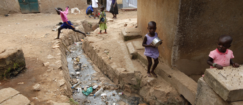 A child leaps across an open sewer in Kisenyi, a slum in Kampala, March 28, 2009.    MALTA OUT. NO COMMERCIAL OR EDITORIAL SALES IN MALTA          REUTERS/Darrin Zammit Lupi (UGANDA) - RTXESAG