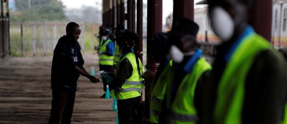 A security guard uses a sprayer to sanitise a commuter hands before he boards a train to prevent the spread of coronavirus disease (COVID-19), at the main railway station in Nairobi, Kenya, March 17, 2020. REUTERS/Baz Ratner - RC2SLF9XEAIG