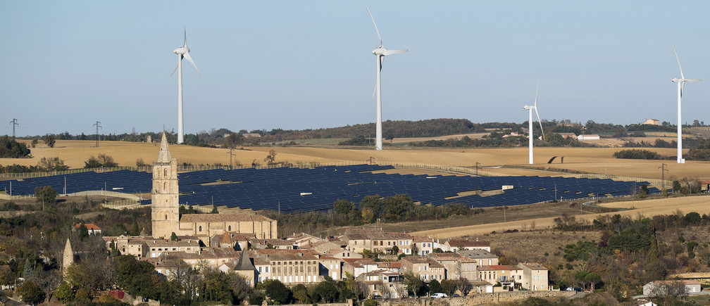 General view shows wind turbines behind rows of solar panels in Avignonet-Lauragais, in the Midi-Pyrenees region, France, October 30, 2015. The mixed site produces electricity from a wind farm of twelve turbines and 20,320 solar panels. France is host to the COP21, the World Climate Summit from November 30 to December 11, 2015. Picture taken October 30, 2015.   REUTERS/Fred Lancelot - LR2EBB40V9UZR
