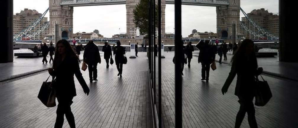 Workers walk through the More London business district with Tower Bridge seen behind in London, Britain, November 11, 2015