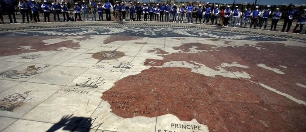 "A group of volunteers gather on a square decorated with a giant world map, during Earth Day celebrations in Lisbon April 22, 2015. Volunteers held placards with letters forming the sentence ""We take care of the Earth"". Earth Day, which promotes awareness and protection of the environment, is celebrated annually on April 22.  REUTERS/Rafael Marchante - GF10000068787"