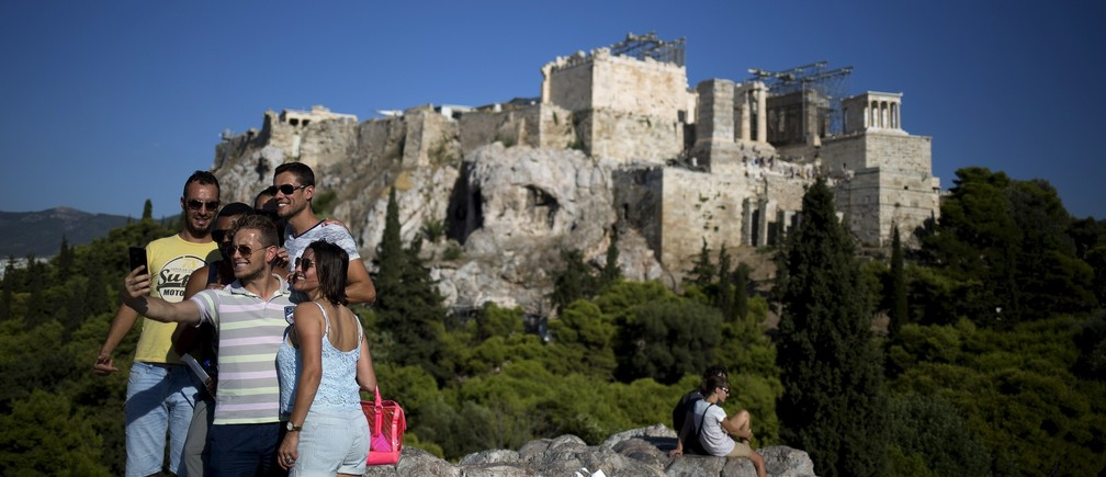 Tourists take a 'selfie' as they visit the hill of Areios Pagos with the archaeological site of the Acropolis in the background in Athens, Greece, August 17, 2015.