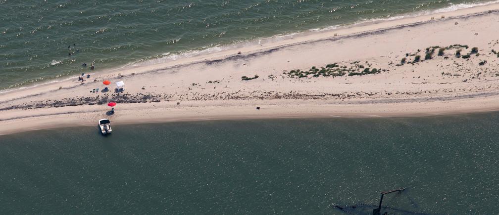 Los visitantes nadan en las aguas a lo largo de un banco de arena en el lado sur de la isla de Tánger, Virginia, EE. UU.