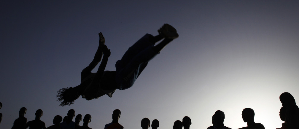 People watch as an acrobat practices flips at Yoff beach in Senegal's capital Dakar, Novermber 1, 2009