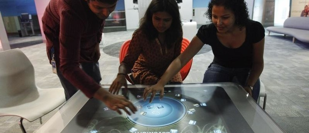 Employees demonstrate the use of the newly-designed prototype of a touch-sensitive table at Microsoft India's Development Center in the Gachibowli IT district in Hyderabad, in the southern state of Andhra Pradesh March 6, 2012. Picture taken on March 6, 2012. REUTERS/Vivek Prakash (INDIA - Tags: BUSINESS SOCIETY EMPLOYMENT SCIENCE TECHNOLOGY) - GM1E8450XD101