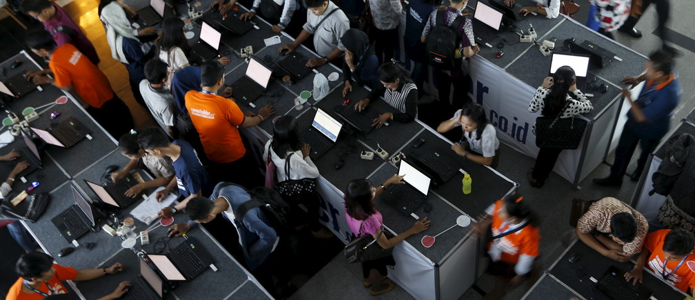 Indonesian youths fill up job application forms on laptops during the Career & Higher Education Fair in Jakarta, April 10, 2015.