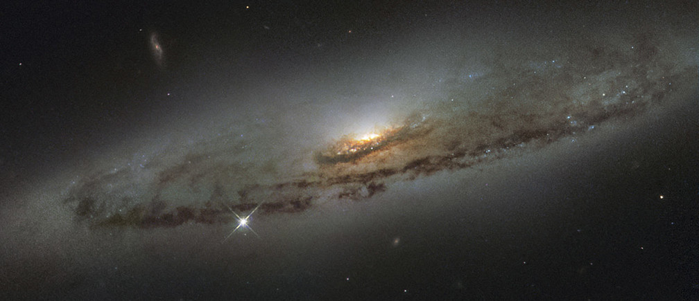 The spiral galaxy NGC 4845, located over 65 million light-years away in the constellation of Virgo (The Virgin) is shown in this NASA/ESA Hubble Space Telescope image released on January 8, 2016. The galaxy?s orientation clearly reveals the galaxy?s striking spiral structure: a flat and dust-mottled disc surrounding a bright galactic bulge. NGC 4845?s glowing center hosts a gigantic version of a black hole, known as a supermassive black hole. REUTERS/NASA/Handout  FOR EDITORIAL USE ONLY. NOT FOR SALE FOR MARKETING OR ADVERTISING CAMPAIGNS. THIS IMAGE HAS BEEN SUPPLIED BY A THIRD PARTY. IT IS DISTRIBUTED, EXACTLY AS RECEIVED BY REUTERS, AS A SERVICE TO CLIENTS - RTX21KFS