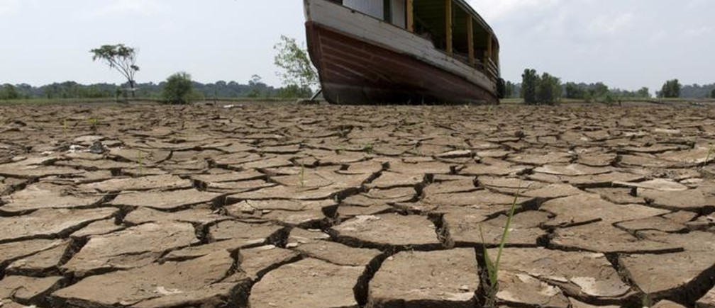 A boat lies on the bottom of Amazonas river, in the city of Manaus, Brazil, October 26, 2015.  A severe drought has pushed river levels in Brazil's Amazon region to lows, leaving isolated communities dependent on emergency aid and thousands of boats stranded on parched riverbeds. REUTERS/Bruno Kelly      TPX IMAGES OF THE DAY