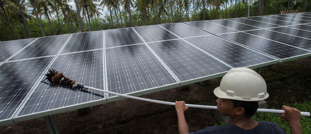 An employee of PT Perusahaan Listrik Negara (PLN) cleans the surface of solar panels at a solar power generation plant in Gili Meno island, in this December 9, 2014 photo taken by Antara Foto. REUTERS/Antara Foto/Widodo S. Jusuf./File Photo ATTENTION EDITORS - FOR EDITORIAL USE ONLY. THIS IMAGE HAS BEEN SUPPLIED BY A THIRD PARTY. MANDATORY CREDIT. INDONESIA OUT.  - S1BEUKLBNJAA