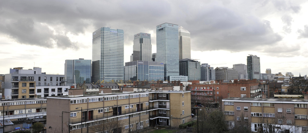 The buildings of the Canary Wharf financial district tower over Poplar, in East London March 27, 2010.