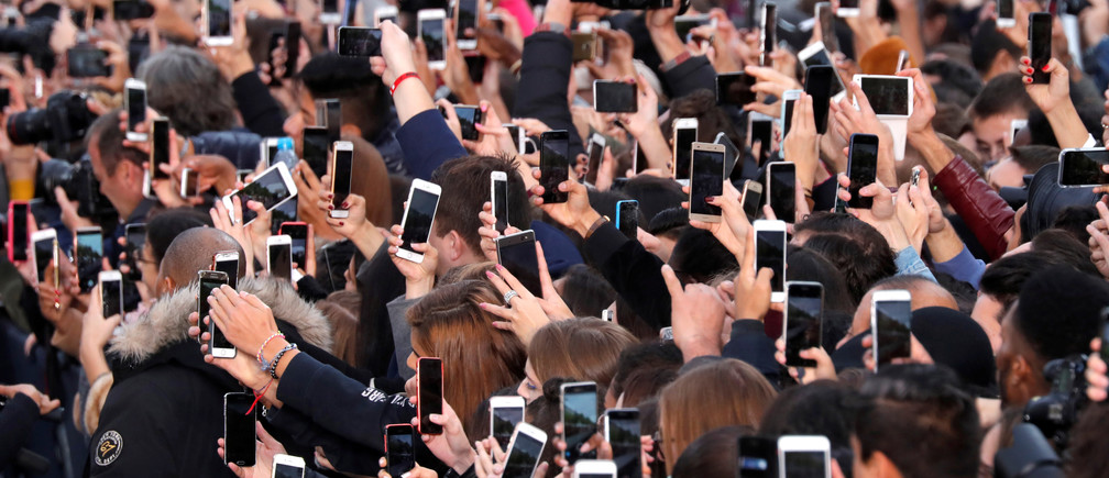 People use their smartphone to take photos of the L'Oreal fashion show on the Champs Elysees avenue during a public event organized by French cosmetics group L'Oreal as part of Paris Fashion Week, France, October 1, 2017.  REUTERS/Charles Platiau     TPX IMAGES OF THE DAY - RC1CAB6813E0