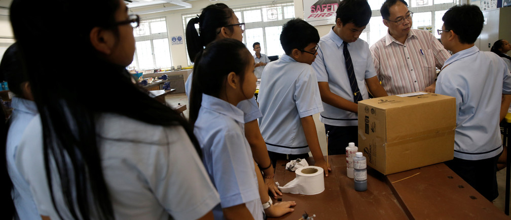 A teacher supervises students as they spray paint a model aeroplane during an enrichment class at a secondary school in Singapore October 27, 2016. Picture taken October 27, 2016. REUTERS/Edgar Su