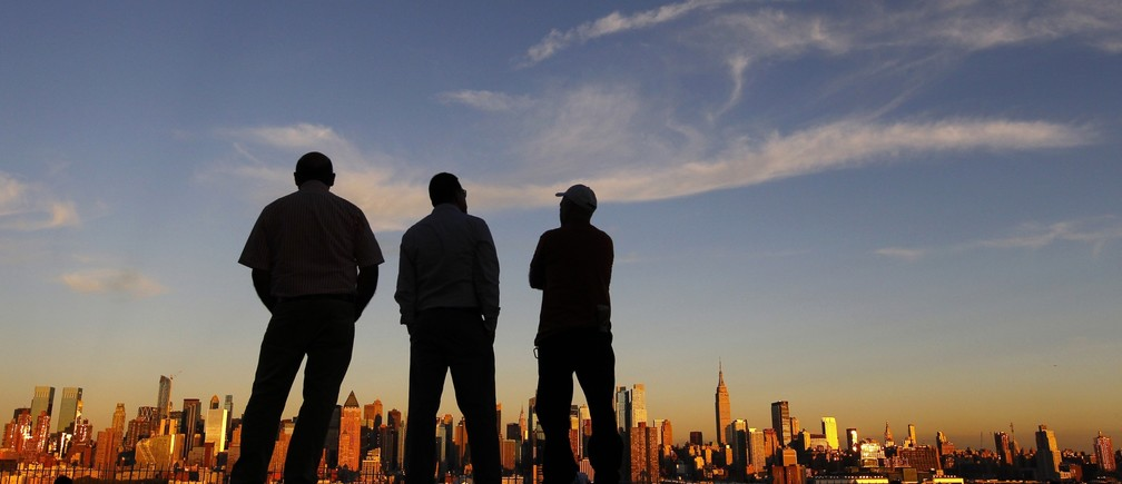 People watch the sun set over New York from a park in Weehawken, New Jersey September 8, 2013.