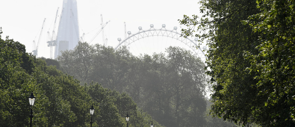 Members of the Household Cavalry are seen, with the London Eye wheel and Shard skyscraper behind, riding in the early morning in Hyde Park in London, Britain, May 11, 2018. REUTERS/Toby Melville - RC15105A4F60