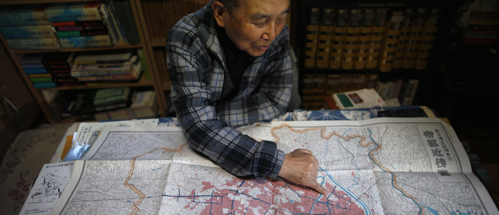 """Japanese Katsumoto Saotome, 82, a survivor of Great Tokyo Air Raids in 1945, points to a map showing the burned central Tokyo areas in red after the bombing, during an interview with Reuters at his home in Tokyo March 4, 2015. Now, as memories fade of how civilians suffered during World War Two - suffering Saotome blames on Japan's wartime leaders who thought of their citizens as """"weeds"""" - the author fears Japan may be marching towards war again. Picture taken March 4. REUTERS/Issei Kato (JAPAN - Tags: CONFLICT ANNIVERSARY POLITICS) - RTR4SJOQ"""