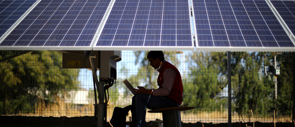 An engineer works under solar panels at a solar plant near Santiago, Chile, May 2017