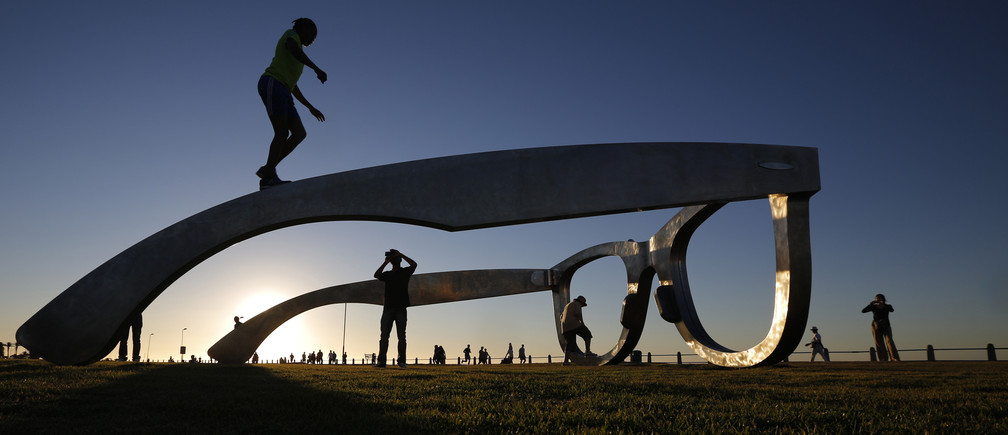 Youths pose for photographs as they climb on top of a sculpture in the form of a giant pair of spectacles on Cape Town's Sea Point Promenade, November 18, 2014.  Inspired by Nelson Mandela, the work  'Perceiving Freedom' by artist Michael Elion has stirred some controversy in the local media. While popular with visitors to the promenade, some critics have questioned the association of Mandela's legacy with commercial sponsors.  REUTERS/Mike Hutchings (SOUTH AFRICA - Tags: SOCIETY TPX IMAGES OF THE DAY) - GM1EABJ0FR001