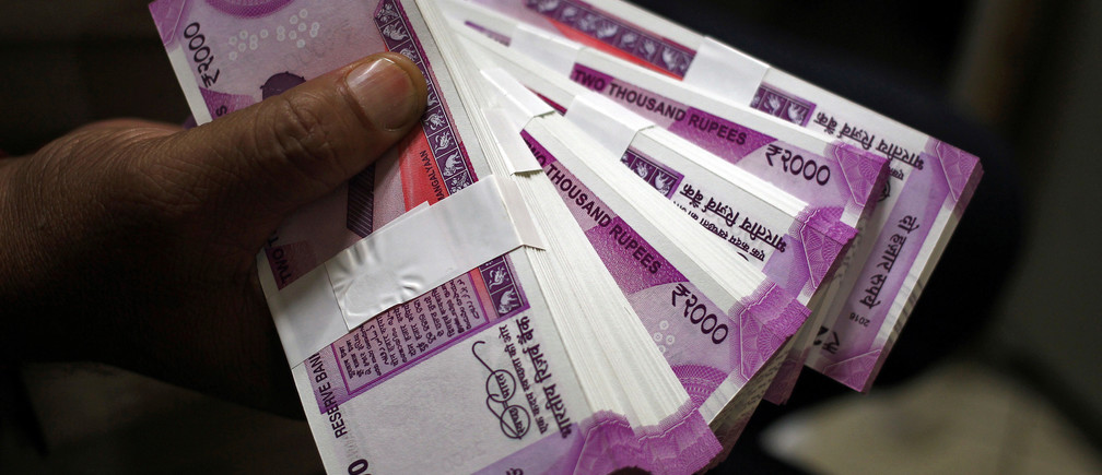FILE PHOTO: A cashier displays the new 2000 Indian rupee banknotes inside a bank in Jammu, November 15, 2016. REUTERS/Mukesh Gupta/File photo - RC1A7387D600