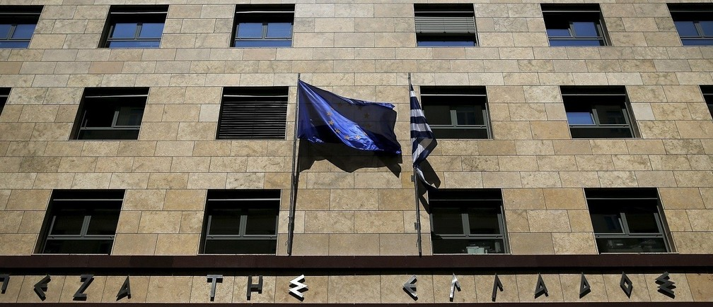 "A European Union flag (L) flutters next to a Greek flag on the facade of the Bank of Greece headquarters in Athens April 14, 2015. Greece denied on Monday a report by the Financial Times that it was preparing for a debt default if it did not reach a deal with its creditors by the end of the month and said the negotiations were proceeding ""swiftly"" towards a solution."