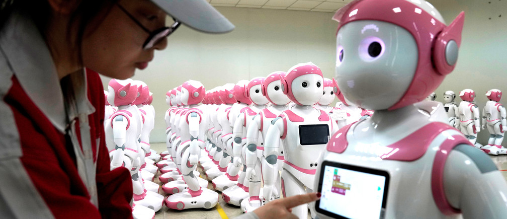 A worker puts finishing touches to an iPal social robot, designed by AvatarMind, at an assembly plant in Suzhou, Jiangsu province
