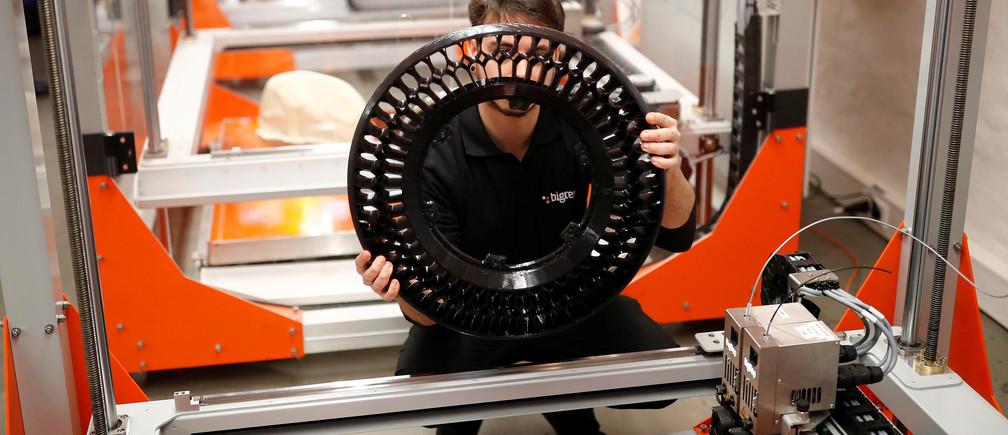 A designer checks a 3D-printed wheel of a motorcycle.