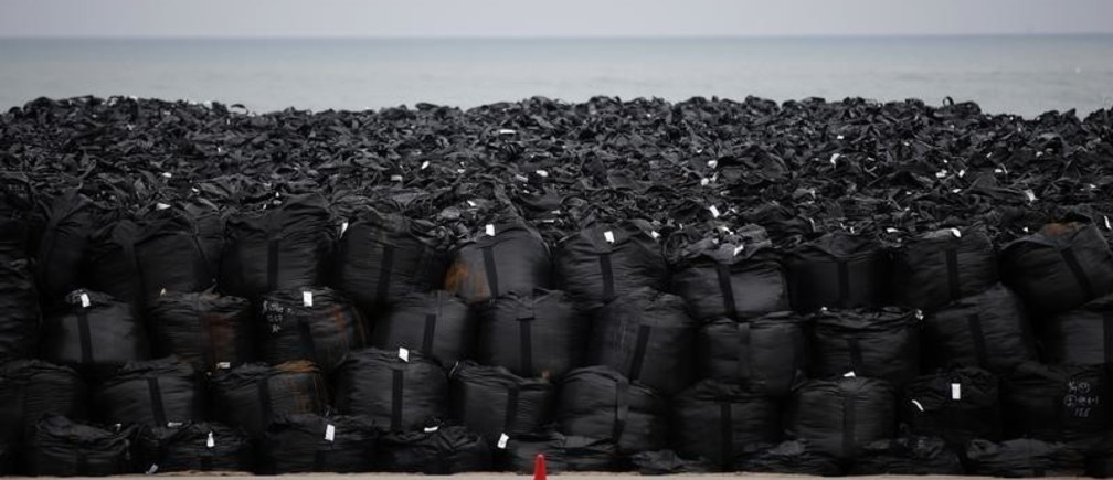 Big black plastic bags containing radiated soil, leaves and debris from the decontamination operation are dumped at a seaside, devastated by the March 11, 2011 earthquake and tsunami in Tomioka town, Fukushima prefecture, near Tokyo Electric Power Co's (TEPCO) tsunami-crippled Fukushima Daiichi nuclear power plant February 22, 2015. Many residents of Okuma, a village near the stricken Fukushima Daiichi plant, are angry about government plans to dump some 30 million tons of radioactive debris raked up after the March 2011 nuclear disaster in a sprawling waste complex on their doorstep. Few believe Tokyo's assurances that the site will be cleaned up and shut down after 30 years. In the four years since the disaster, Japan has allocated over $15 billion to lower radiation levels around the plant. Every day, teams of workers blast roads with water, scrub down houses, cut branches and scrape contaminated soil off farmland. That radiated trash now sits in plastic sacks across the region, piling up in abandoned rice paddies, parking lots and even residents' backyards.  REUTERS/Toru Hanai (JAPAN - Tags: DISASTER ENERGY ENVIRONMENT TPX IMAGES OF THE DAY) PICTURE 17 OF 27 FOR WIDER IMAGE STORY 'RADIOACTIVE FUKUSHIMA - FOUR YEARS ON'SEARCH 'OKUMA TORU' FOR ALL IMAGES - LM2EB350YX801