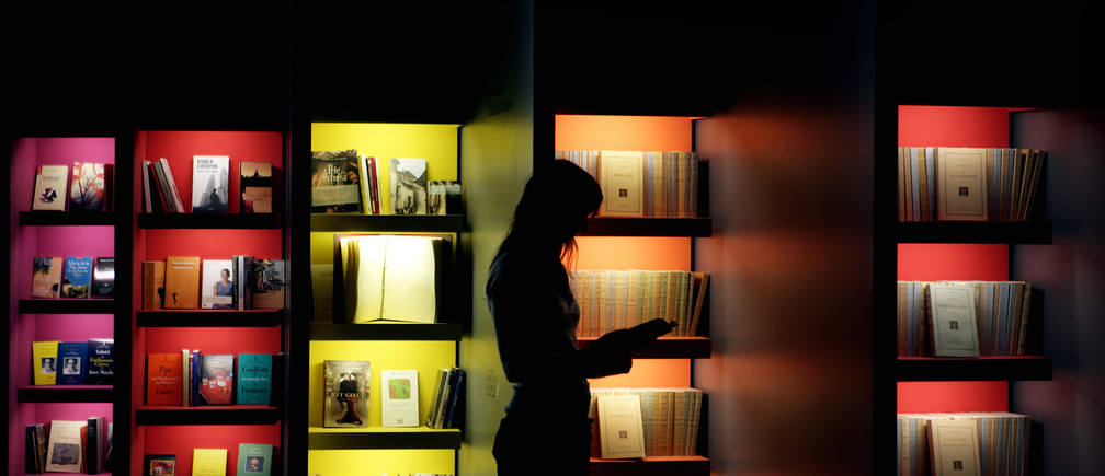 "A woman looks into a book at the exhibition of ""Catalan culture"", the guest of honour at the Frankfurt book fair, October 9, 2007. The world's largest bookfair will be open to public from October 10 to October 14.  REUTERS/Kai Pfaffenbach (GERMANY) - BM2DWIHPCJAA"