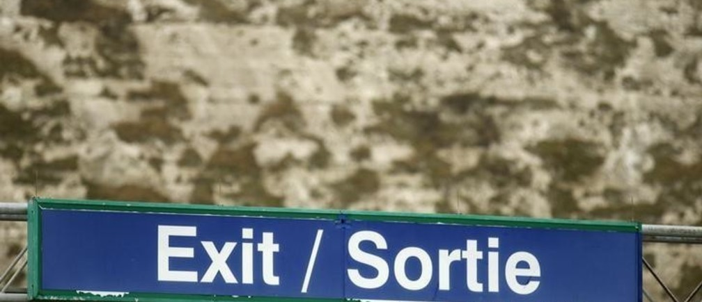 An exit sign printed in English and French is seen in front of the White cliffs of Dover, at the Dover ferry terminal, Britain February 20, 2016. Stand on top of the white cliffs of Dover on a clear day and you can see the French coast and the constant traffic of ferries crossing the Channel, binding Britain and Europe through the flow of people and goods. Seen through many British eyes, the famous cliffs conjure up a different vision, that of a fiercely independent island nation with a nearly thousand-year history of repelling would-be invaders from the continent just 33 km (21 miles) away. The tension between these two facets of British identity goes a long way to explain the country's tetchy relationship with the European Union, which will come to a head in a looming referendum on whether to withdraw from the bloc. Photograph taken on February 20, 2016.  REUTERS/Phil Noble