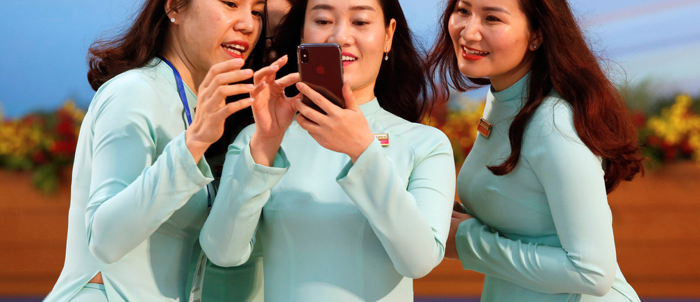 Vietnamese women wearing the traditional 'dao dai' long dress take a selfie at the National Convention Centre in Ha Noi, Viet Nam, March 2018.