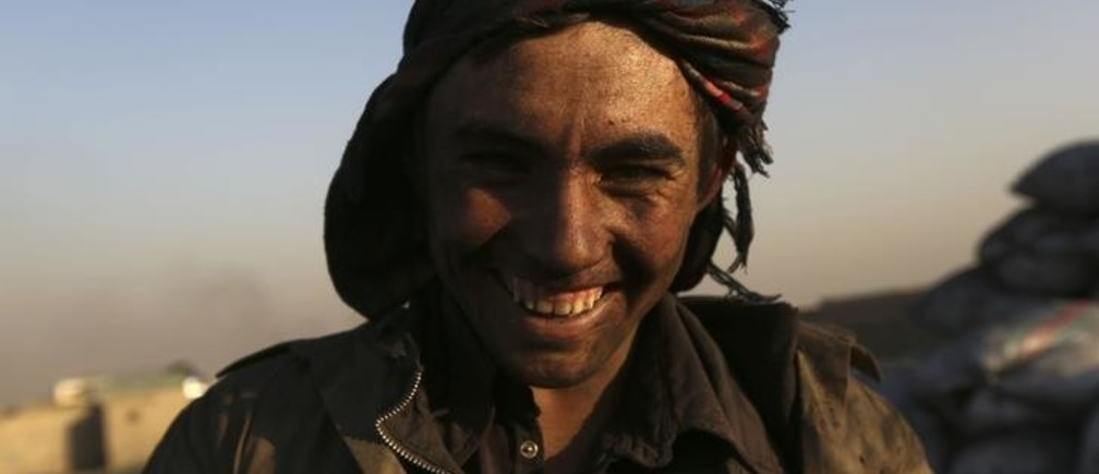 A labourer smiles as he takes a break from shoving coal at a coal dump site outside Kabul December 4, 2012.  REUTERS/Omar Sobhani (AFGHANISTAN - Tags: SOCIETY BUSINESS EMPLOYMENT)