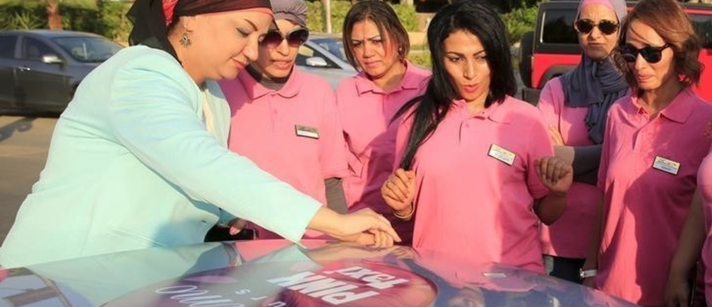 Reem Fawzy (L), the director of the Pink Taxi company, stands with her drivers in a parking lot in Cairo, Egypt, September 6, 2015. Pink uniforms, a pink logo on the cars, and even pink nail polish - it's all part of the look of women-drivers working for Egypt's first women-only taxi service. The Pink Taxi company hires only women drivers and gives rides to only female passengers. The company was started in an effort to provide a safe taxi service for women in a country with high rates of sexual harassment, said Fawzy. Picture taken September 6, 2015. REUTERS/Amr Abdallah Dalsh