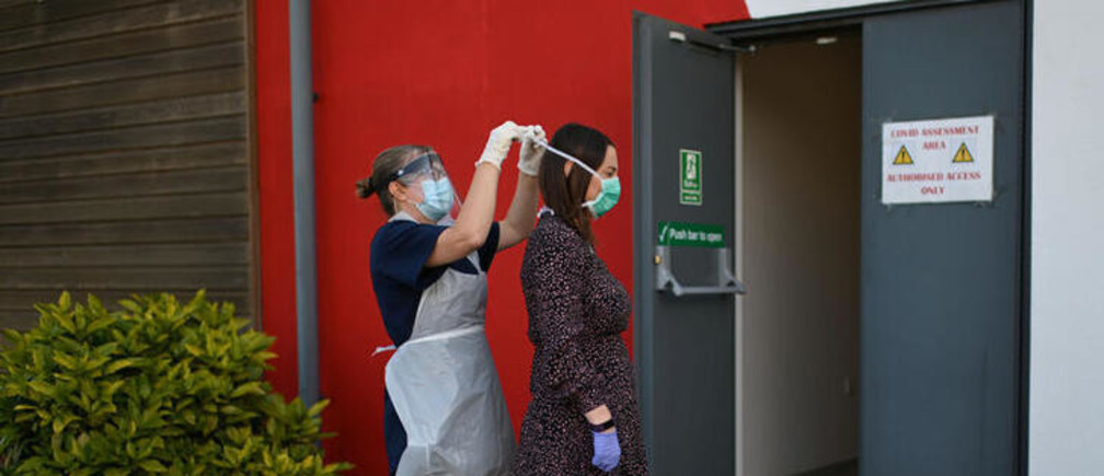 Nurse Lucy Wraith wearing personal protective equipement (PPE) ties a surgical mask around Chloe Allison's head as they test the measures taken by the practice to receive suspected coronavirus patients at Freshney Green Primary Care Centre in Grimsby, Britain June 9, 2020. Picture taken June 9, 2020. Daniel Leal-Olivas/Pool via REUTERS