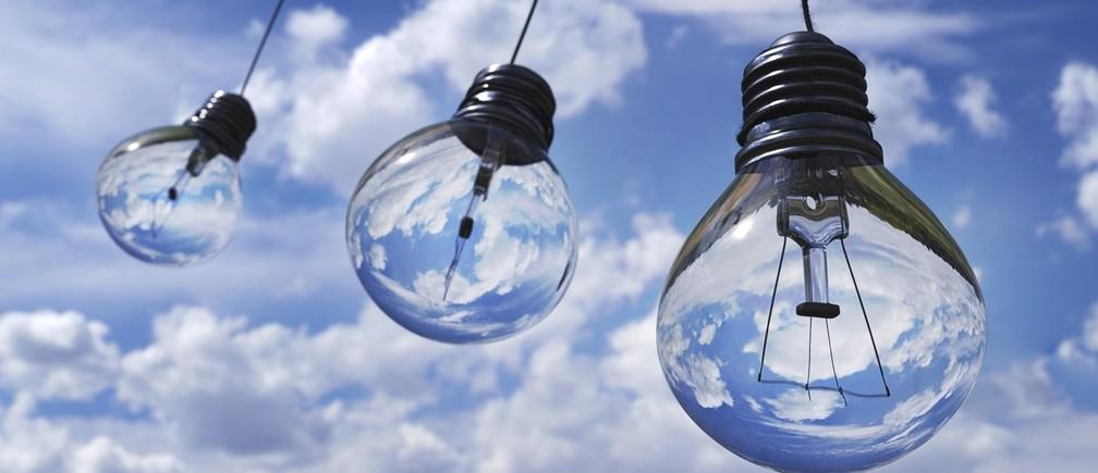 Three transparent light bulbs against a blue sky