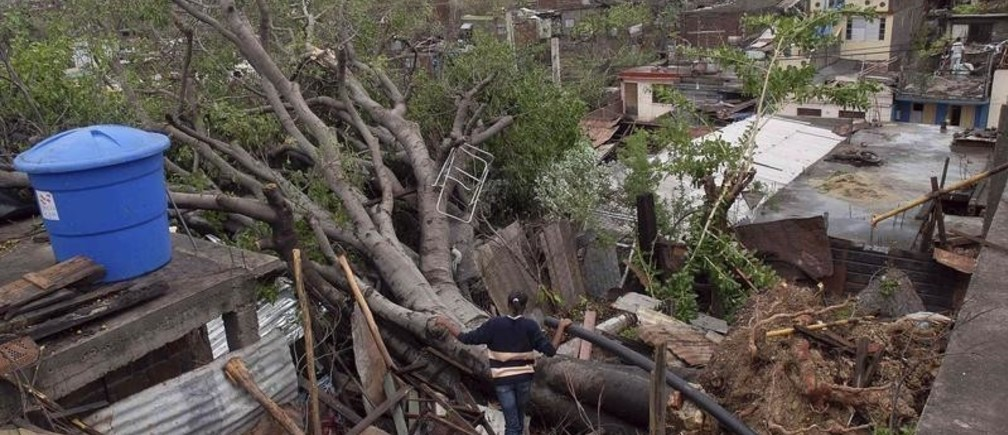 A woman looks at a fallen tree on top of her house after Hurricane Sandy hit Santiago de Cuba October 25, 2012. Strengthening rapidly after tearing into Jamaica and crossing the warm Caribbean Sea, Sandy hit southeastern Cuba early on Thursday with 105-mph winds that cut power and blew over trees across the city of Santiago de Cuba. Reports from the city of 500,000 people, about 470 miles (750 km) southeast of Havana spoke of significant damage, with many homes damaged or destroyed. REUTERS/Miguel Rubiera/Cuban Government National Information Agency-AIN/Handout (CUBA - Tags: ENVIRONMENT DISASTER) FOR EDITORIAL USE ONLY. NOT FOR SALE FOR MARKETING OR ADVERTISING CAMPAIGNS. THIS IMAGE HAS BEEN SUPPLIED BY A THIRD PARTY. IT IS DISTRIBUTED, EXACTLY AS RECEIVED BY REUTERS, AS A SERVICE TO CLIENTS - GM1E8AQ08JM01