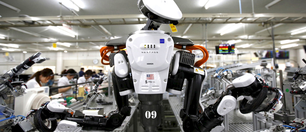 A humanoid robot works side by side with employees in the assembly line at a factory of Glory Ltd., a manufacturer of automatic change dispensers, in Kazo, north of Tokyo, Japan, July 1, 2015.