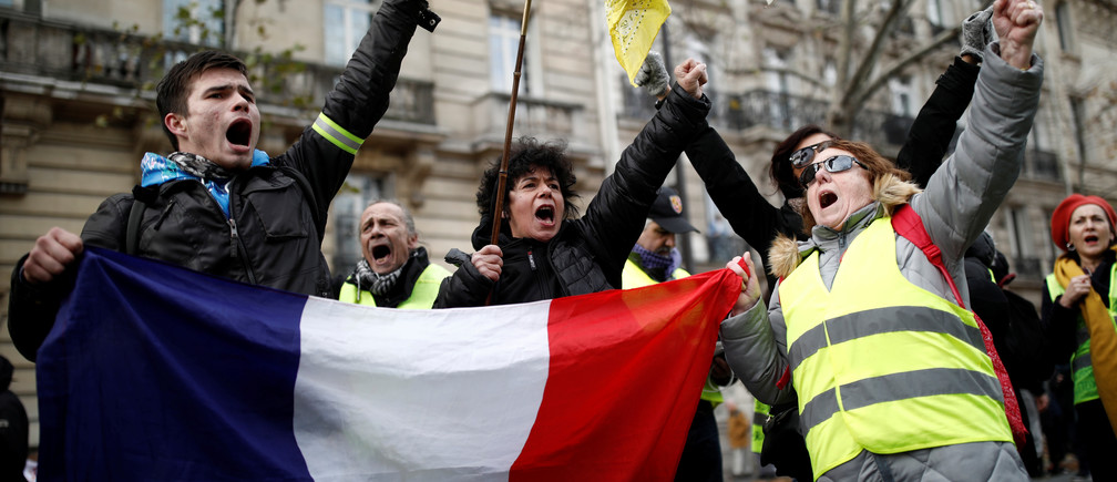 Protestors wearing yellow vests hold a French flag during a demonstration against French government's pensions reform plans in Paris as part of a second day of national strike and protests in France, December 10, 2019. REUTERS/Benoit Tessier - RC2DSD9VOPFP