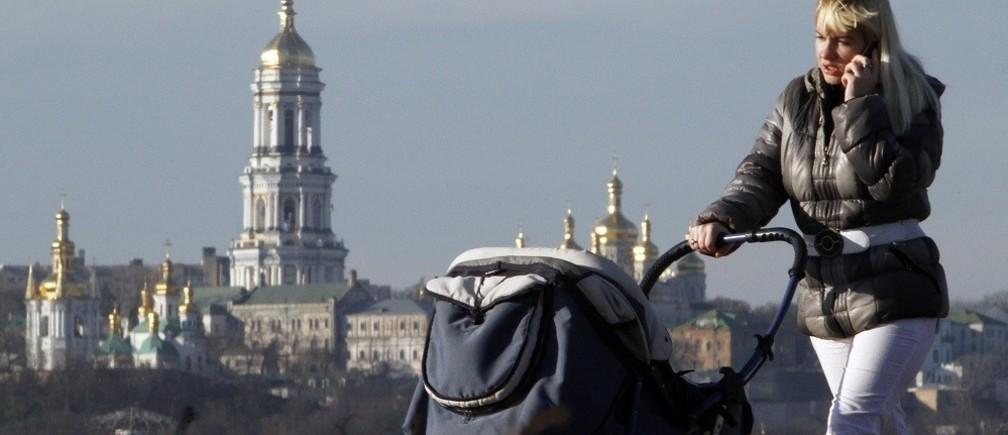 A woman pulls a baby cart, with the Kievo-Pecherskaya Lavra seen in the background, in Kiev November 30, 2012. REUTERS/Anatolii Stepanov (UKRAINE - Tags: CITYSPACE SOCIETY) - RTR3B28L