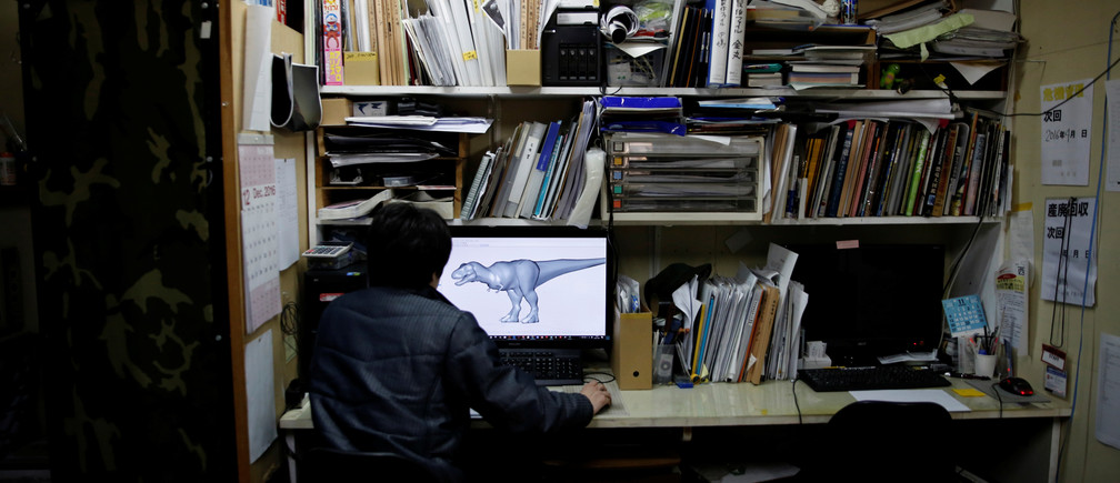 Japan's ON-ART Corp's staff looks at a simulation of dinosaur robot's movement on the computer at the company's studio in Tokorozawa, Japan, December 6, 2016. Picture taken December 6, 2016.   REUTERS/Toru Hanai - RTX2VXVE
